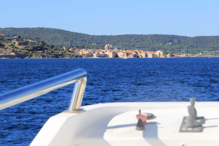 tropez: Distant view of Saint Tropez on the Mediterranean coast of France seen from an approaching ferry boat in blurred foreground