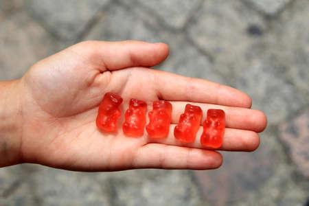 gummi: Childs hand open palmed holding five red gummi bears