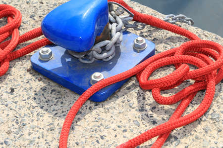 Closeup of blue harbour bollard with red rope on a concrete harbour quayside Stock Photo