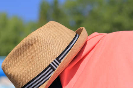 pool side: Straw trilby hat on sunny pool side with pink shirt