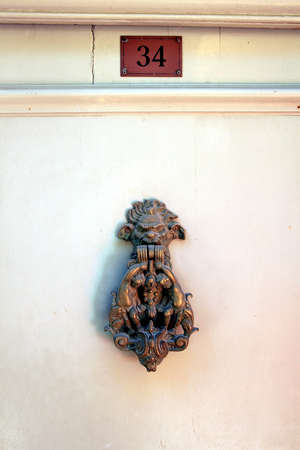 cherubs: Gothic door knocker with cherubs and monster face and number thirty four