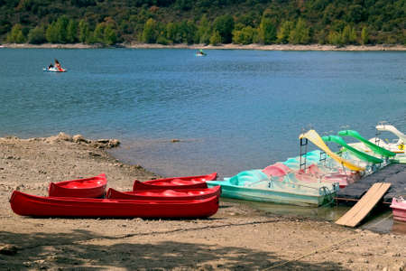 Pedallos and kayaks on the rocky shore of a freshwater lake, with lakeshore trees in distance