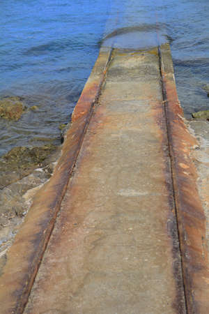 boathouse: Rusty old iron and stone slipway leading from boathouse to the blue water Stock Photo