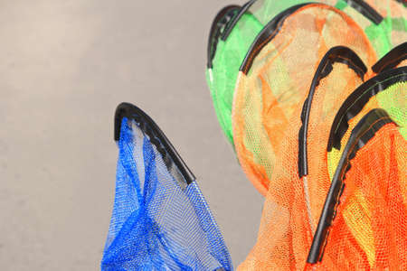 shop for animals: Kids fishing nets stacked for sale, orange, blue, green,shallow focus Stock Photo