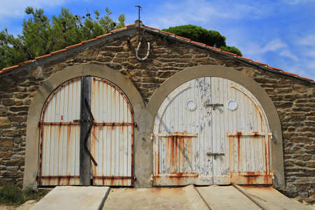 boat house: Rustic old provencal boat house with white wooden doors on a bright sunny day