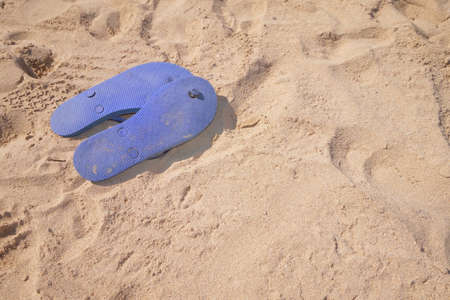 upturned: Flip flops upturned on beach sand with copy space