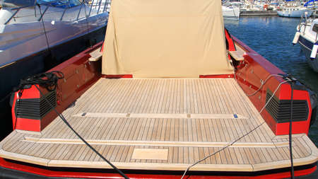 buffed: Modern red motor boat from rear with wide wooden deck and canvas Stock Photo
