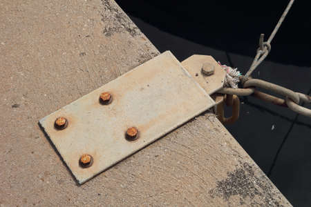 attached: Steel mooring point on quayside with chain attached