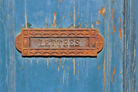 flaky: Traditional French rusty iron letter box on grungy blue flaky painted wooden door