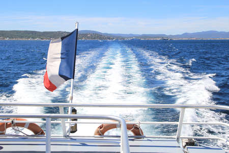tricolour: French tricolour flag flying on the back of a boat leaving a wake through the blue Mediterranean sea in summer