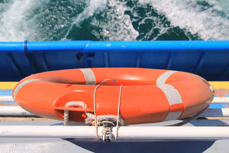 marina life: Lifebelt on rear of a boat, with white foam of the wake in background Stock Photo
