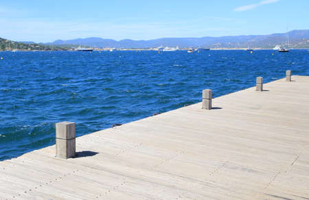 bollards: wooden boat mooring bollards on jetty by blue ocean Stock Photo