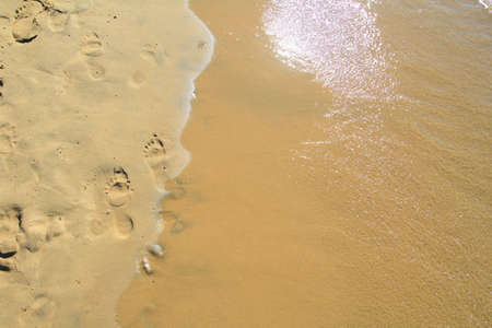 Footprints on a sandy beach being washed away by the sea with the sun reflecting in the waves Archivio Fotografico