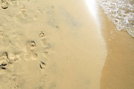 transient: Footprints on a sandy beach being washed away by the sea with the sun reflecting in the waves Stock Photo