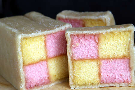 archival: Freshly cut Battenberg Cake slices on wooden board with dark background. Pink and yellow sponge covered in marzipan