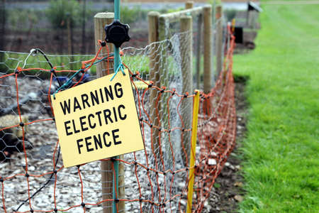 Warning electric fence sign on electric fence Stock Photo