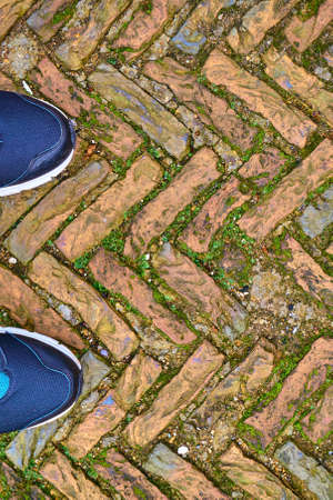 juxtaposition: Toes of modern training shoes standing on old cobble stones in a herringbone pattern Stock Photo