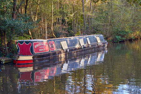 English canal narrow boat with Autumn fall leaves on trees