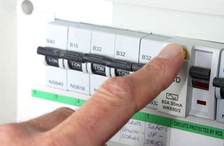 Testing an RCD (Residual Current Device) on a UK domestic electrical consumer unit or fuse box Archivio Fotografico