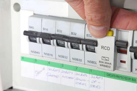 Het testen van een RCD (aardlekschakelaar) op een Britse huishoudelijke elektrische consument eenheid of zekeringkast Stockfoto