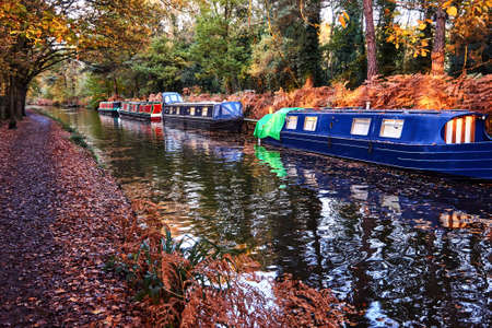 English canal narrow boats with Autumn fall leaves on trees