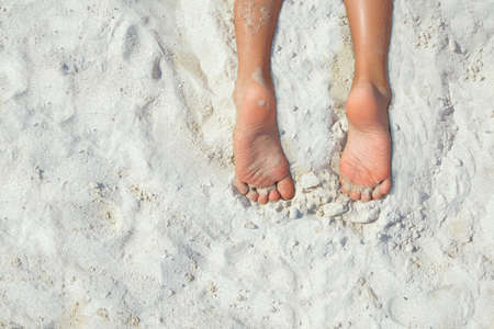 sandy brown: Brown feet and lower legs on white sandy beach in sunshine. Space for text