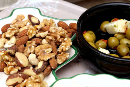 Olives, feta cheese, crisps, walnuts, almonds, cashew nuts, brazil nuts and hazelnuts served with an aperitif Stock Photo