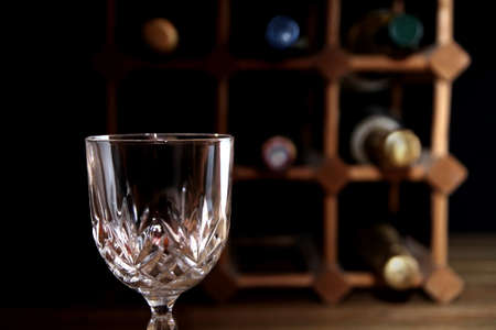 Empty wine glass with wooden wine rack in blurred background Stock Photo