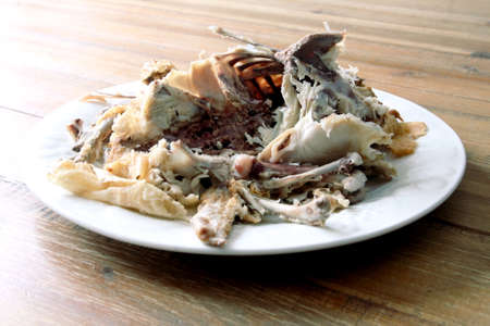 chest cavity: Roast chicken carcass remains on a plate on a wooden table