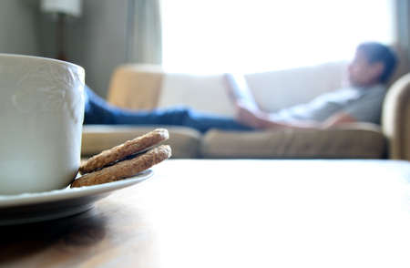 Tea and biscuits or cookies on a wooden coffee table, man relaxing on sofa in blurred background. Space for copy text.