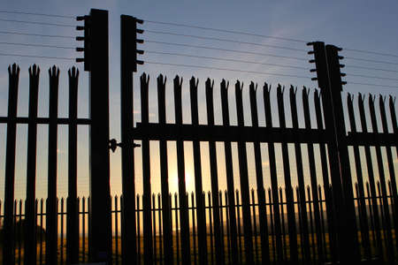 unreachable: High security steel and razor wire fence, with unreachable sunset landscape behind it
