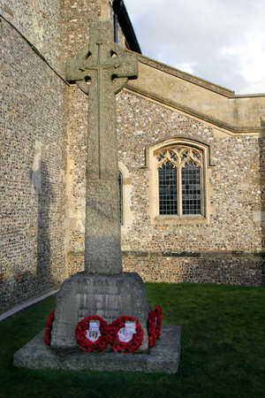 New Alresford, UK - Jan 28 2017: Celtic cross with poppy wreaths commemorating fallen soldiers outside St Johns Church at New Alresford in Hampshire UK. Editorial