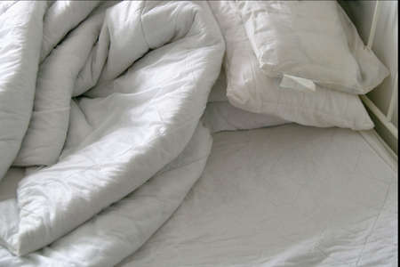 unmade: Duvet and pillows on an unmade bed