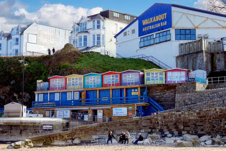Newquay, Cornwall, UK - April 1 2017: Colourful beach huts above Newquay beach, in front of the Walkabout Australian Bar - unidentified people enjoy the beach