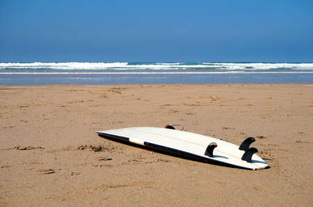 White surfboard abandoned on an empty sandy beach with waves in distance