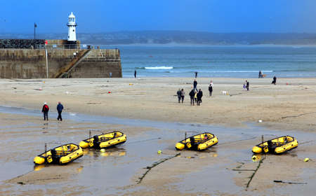 St Ives, Cornwall, UK - 3rd April 2017: People walking past inflatable dinghies belonging to St Ives Self Drive Boat hire in the harbour at low tide