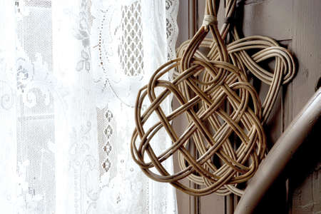 Old traditional carpet beaters hanging in the window with net curtains Фото со стока