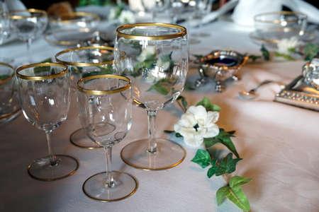 Antiguos vasos de oro con bordes en una mesa de comedor adornada Foto de archivo - 78422268