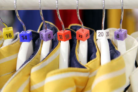 Closeup of various clothes size markers on a row of yellow jackets