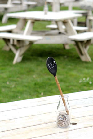 Table number marker on an outside wooden restaurant table