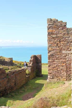 A young girl explores the ruins of a Cornish tin mine in England near the Atlantic coast Stock Photo