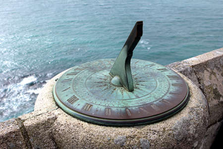 Antique sundial on a stone wall overlooking the sea Archivio Fotografico