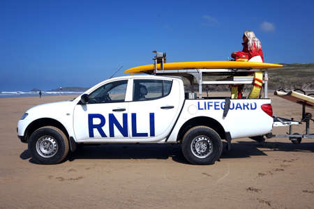 Newquay, Cornwall, UK - April 7 2017: Female RNLI lifeguard keeping watch on top of a truck on a surfing beach in Newquay
