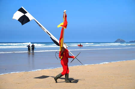 Newquay, Cornwall, UK - April 7 2017: Female RNLI lifeguard moving the swimming and surfing zone flags as the tide comes in