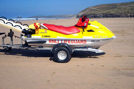 Newquay, Cornwall, UK - April 7 2017: RNLI lifeguard Jetski on a trailer on a surfing beach in Newquay Newquay, Cornwall, UK - August 7 2017: Female RNLI lifeguard keeping watch on top of a truck on a surfing beach in Newquay