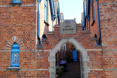 altruismo: Padstow, Cornualles, Reino Unido - 6 de abril de 2017: Casas victorianas de las limosnas del ladrillo rojo, con fecha de 1875, construidas por los benefactores ricos para contener a pobres Editorial
