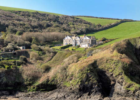 Port Isaac, Cornwall, UK - April 8th 2017: View across the harbour to a large private residence