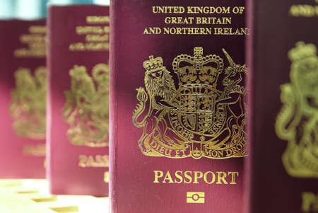 Five British United Kingdom European Union Biometric passports standing in a queue in shallow focus Stock Photo