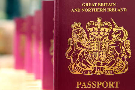 Five British United Kingdom European Union Biometric passports queueing in a line in shallow focus