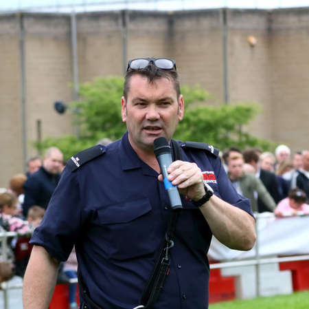 combustible: Beaulieu, Hampshire, UK - May 29 2017: Fire Dog handler of the Hampshire Arson Task Force addressing the crowd during the 2017 999 Show